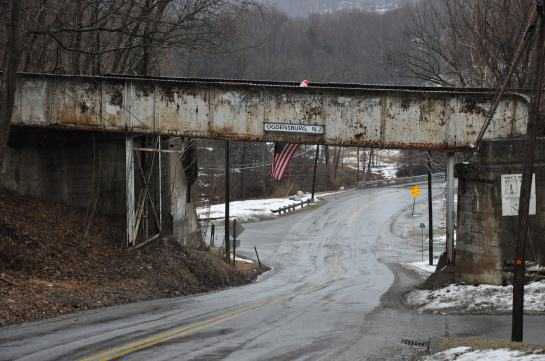 """A rusty, old railroad trestle crossing a backroad. It is winter. There are no leaves on the trees. Snow is on the ground, but the road itself it wet. It is probably just above freezing. As sign that reads """"Ogdensberg NJ"""" is affixed to the trestle. An American flag hangs down from it."""