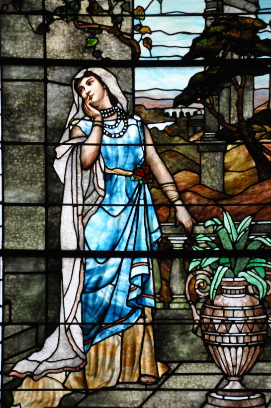 A stained glass window featuring the image of a young woman.