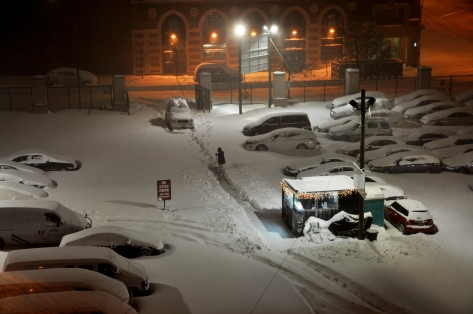 A parking lot in a blizzard in New York City late at night.