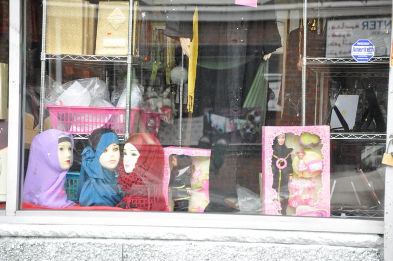A store window with headscarves and a doll.