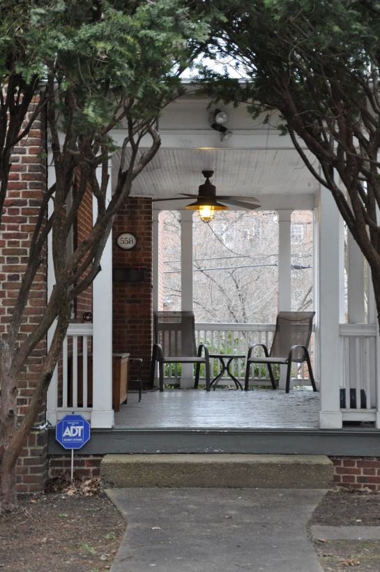 A porch with a couple of chairs.