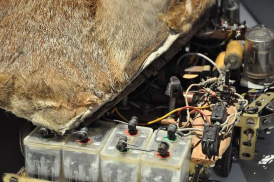 A photograph of an early robot, le renard, french for fox. A dome shaped fur cover has been moved slightly aside to reveal the electronic parts inside.