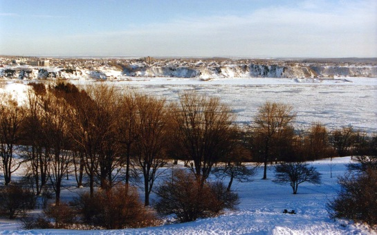 A view of the St. Lawrence River looking south from Quebec City with the river partly frozen and snow on the ground.