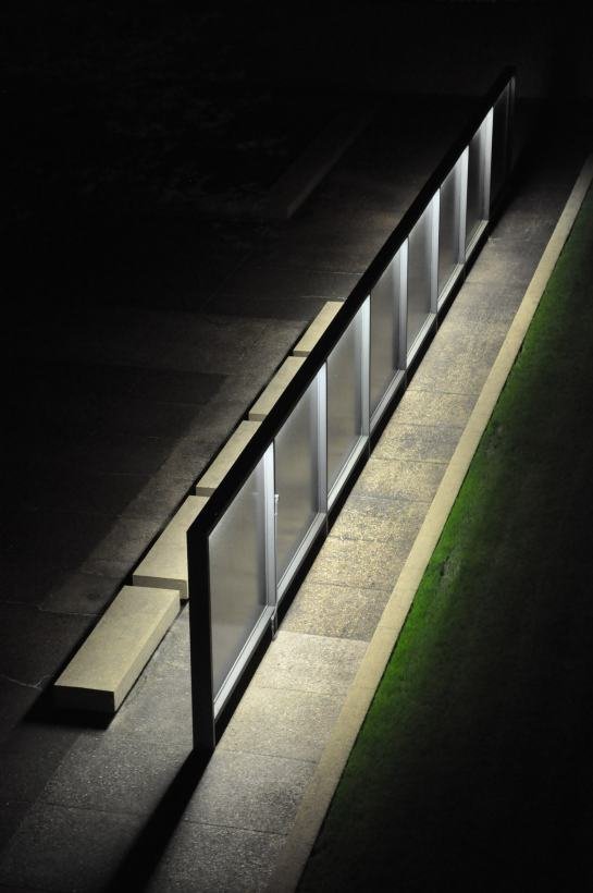 An exterior space designed my Mies Vander Rohe showing the edge of a lawn along a path and some concrete benches.