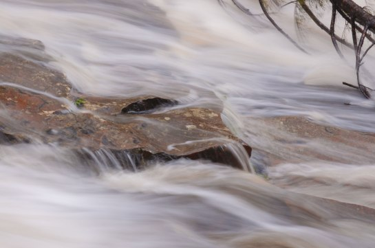 A flat rock in a river speeding rough river with water flowing over it.