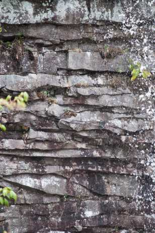 The horizontal pattern in the cliff face edged by spray from the falls.