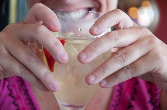 A pair of hands grasping a glass of sangria.