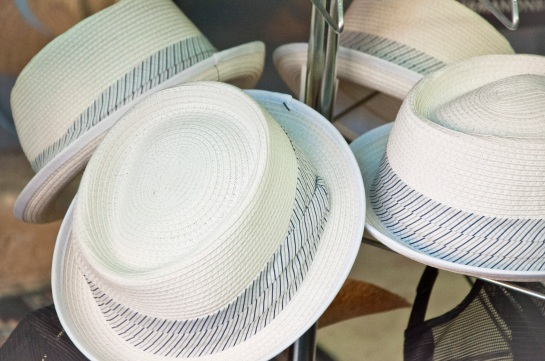 Some men's straw hats for sale on a rack.