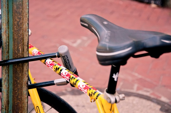 A bike locked to a street sign with elements of the state flag of Maryland painted on it.