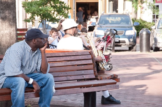 A man in the foreground sitting on a park bench. Behind him, another many plays a saxaphone. In the background is a woman with children. Further yet are some shops with people milling about.