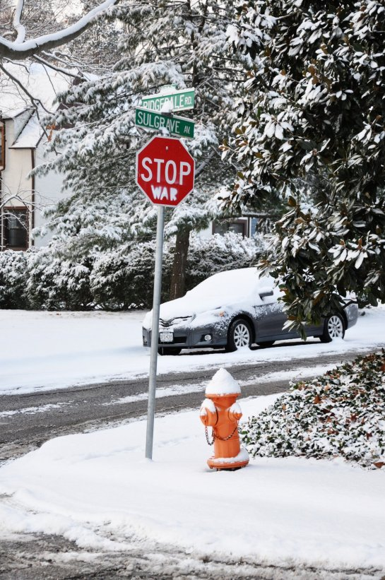"A stop sign on a snow covered street corner in a suburban neighborhood. Beneath the word ""stop"" someone has painted the word ""war"" so the sign now reads ""stop war."""