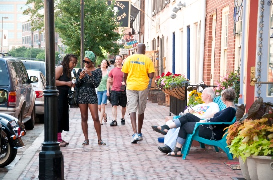 A sidewalk with people walking up and down. In the foregeound, two people sit in chairs in front of a shop and two women look at something on a cell phone together.