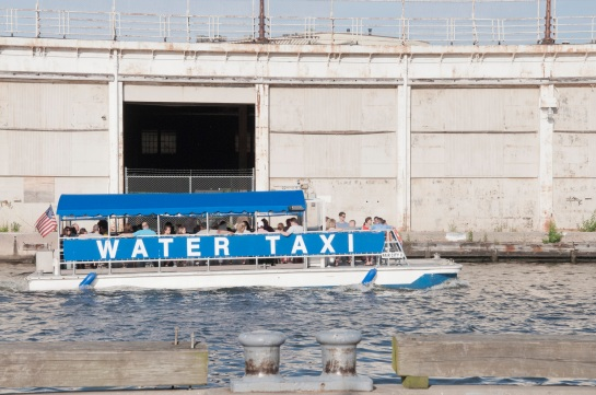 A water taxi passing by an empty warehouse.