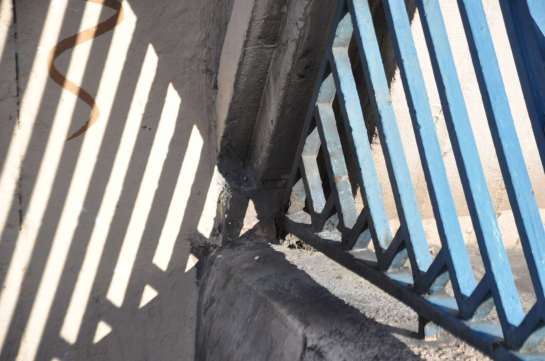This is a photo of the decorative pattern on the railing on the bridge and the shadow it cast on a support.