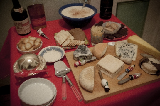 cheese, chocolate, biscotti, liquor, and eggnog arranged on a table.