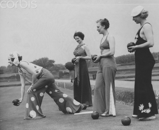 Women bowling on a lawn in trousers.
